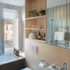 A plywood wall neatly houses various bathroom elements, while shutters avoid the need for frosted glass to the street-facing window